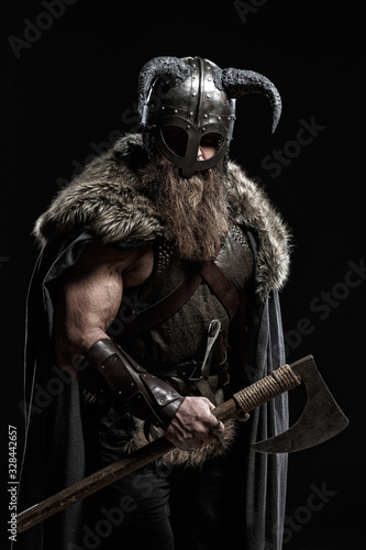 Photo Medieval warrior berserk Viking with axes attacks enemy