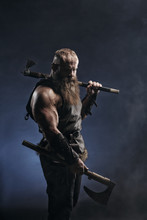 Medieval Warrior Berserk Viking With Axes Attacks Enemy. Concept Historical Photo Of Scandinavian Soldier In Armor And Big Beard