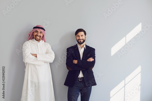 Photo Arab and european businessmen stand smiling at the gray background