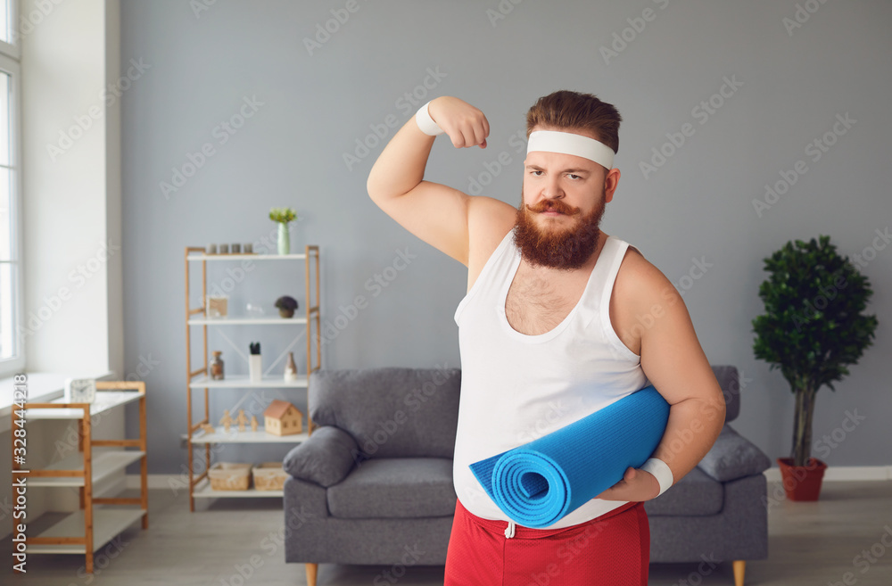 Fototapeta Funny fat man in sportswear shows muscles standing in the room at home