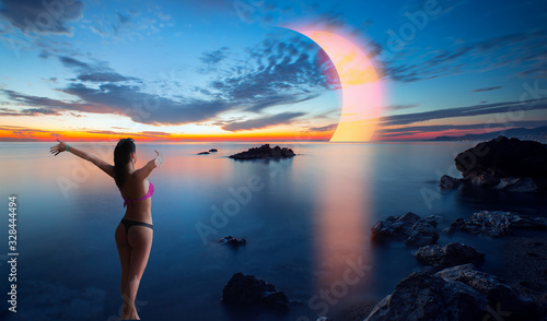 Photographie Long exposure image of Dramatic sky and seascape with rock Solar eclipse over th