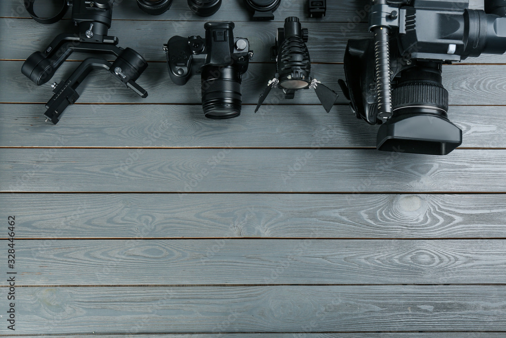 Fototapeta Flat lay composition with video camera and other equipment on grey wooden table. Space for text