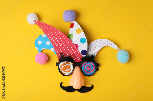 Funny face made of party items on yellow background, flat lay. April Fool's Day
