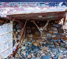 Retro Old Boat Grounded On Bed Of Stones