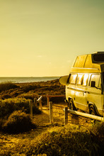 Camper Van With Surf Board On Beach