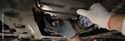 Foto Focus on hardworking male hands examining modern high-tech automobile underneath pipes in white gloves with precise accuracy
