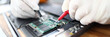 Close-up of circuit board in laptop. Technician soldering microchip using welding machine. Professional at computer service working on pc maintenance. Man in gloves fixing electronics and gadgets