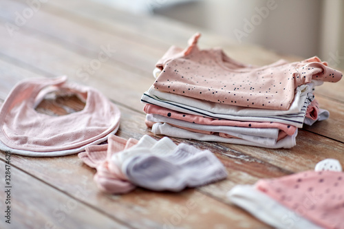 Photo babyhood and clothing concept - baby clothes on wooden table at home