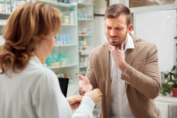 Handsome young man with serious throat ache seeking assistance, buying medications in a pharmacy. Healthcare and medicine concept.
