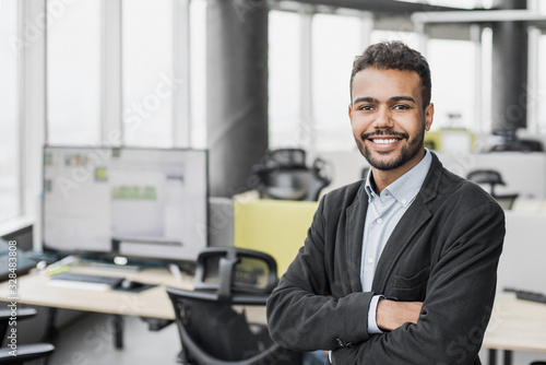 Handsome young businessman with folded arms in the office Poster Mural XXL
