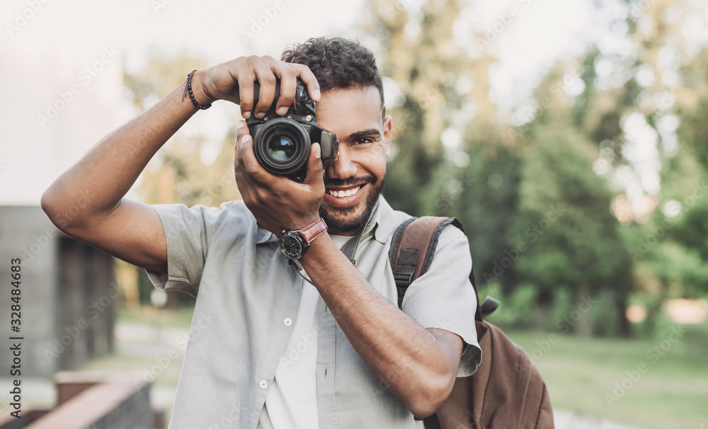 Fototapeta Young man photographer takes photographs with dslr camera in a city. Travel, vacations, professional freelance work and active lifestyle concept