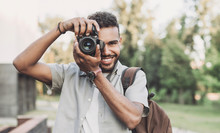 Young Man Photographer Takes Photographs With Dslr Camera In A City. Travel, Vacations, Professional Freelance Work And Active Lifestyle Concept