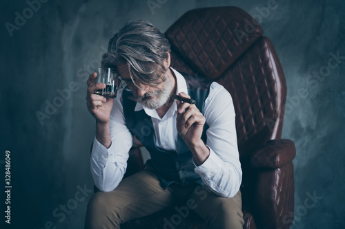 Obraz Portrait of sad old man company owner sit chair hold cigar glass cognac suffer startup fail bad hangover wear white shirt grey vest brown pants trousers isolated concrete wall background - fototapety do salonu