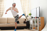 Young handsome man in shorts and vest holds pink dumbbells in hand. Watch tv lessons single combats is practicing receptions of sensei one home fitness indoor training independent education remotely