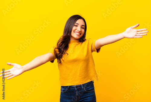 Photo young latin pretty woman smiling cheerfully giving a warm, friendly, loving welc
