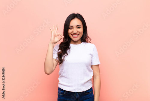 young latin pretty woman feeling happy, relaxed and satisfied, showing approval Wallpaper Mural