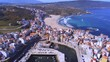 Aerial landscape, Malpica, Small coastal town port on a sunny day, drone wide angle dolly in shot approaching the sandy beach