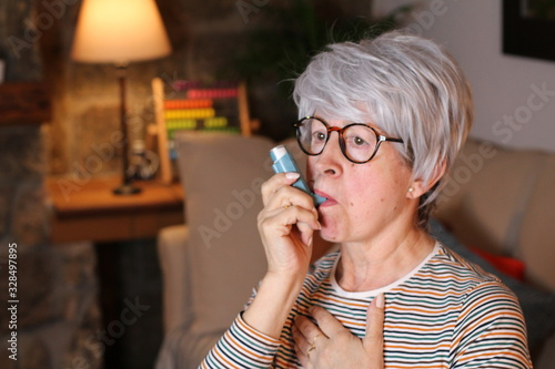 Senior woman using asthma inhaler at home Wallpaper Mural