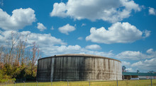 A Huge, Round, Concrete Water Tank In A Green Field Under Blue Skies Beyond A White Fence