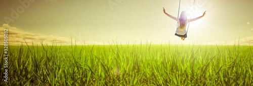 Frau schaukelt über einer Wiese Fototapet
