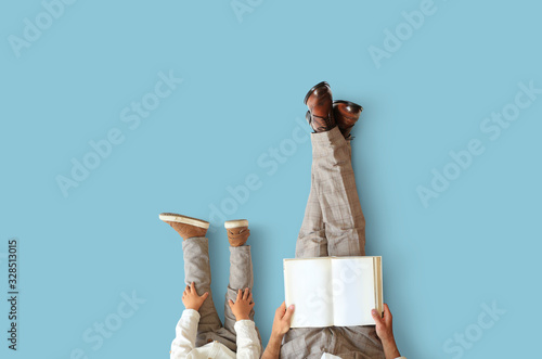Obraz Father and young son sit and read a book - fototapety do salonu
