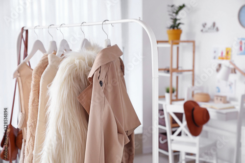 Canvas Rack with stylish female clothes in dressing room
