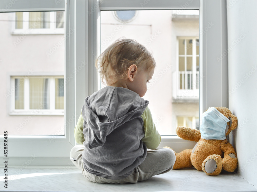 Fototapeta Child in home quarantine standing at the window with his sick teddy bear wearing a medical mask against viruses during coronavirus and flu outbreak. Children and illness COVID-2019 disease concept