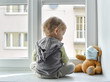 canvas print picture - Child in home quarantine standing at the window with his sick teddy bear wearing a medical mask against viruses during coronavirus and flu outbreak. Children and illness COVID-2019 disease concept