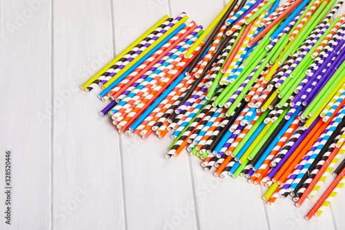 Heap of colorful paper straws for party cocktails on the wooden background Wallpaper Mural
