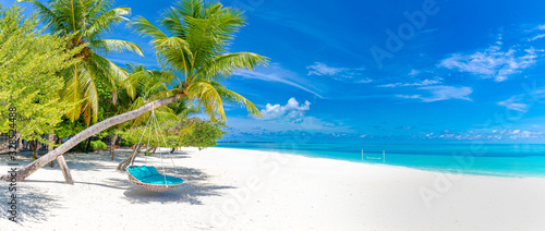 Foto Tropical beach panorama as summer landscape with beach swing or hammock and white sand and calm sea for beach banner