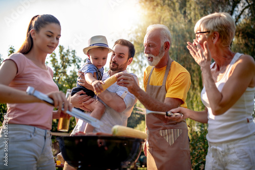 Happy family barbecuing meat on the grill Wallpaper Mural