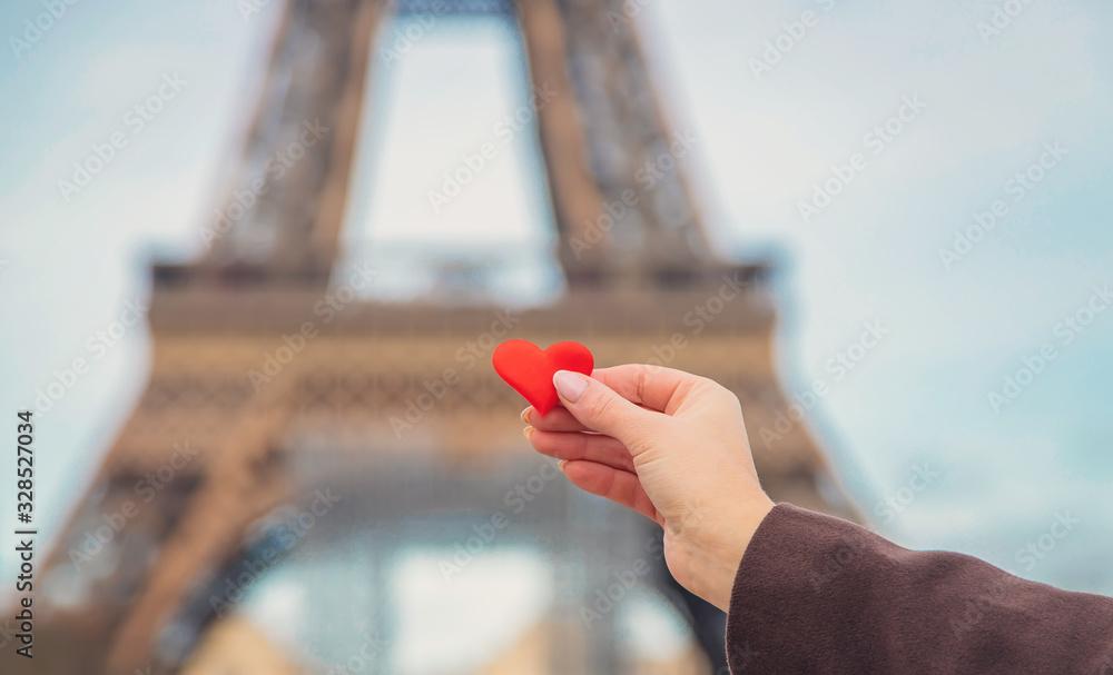 Fototapeta Heart in hands near the Eiffel Tower in Paris. Selective focus.