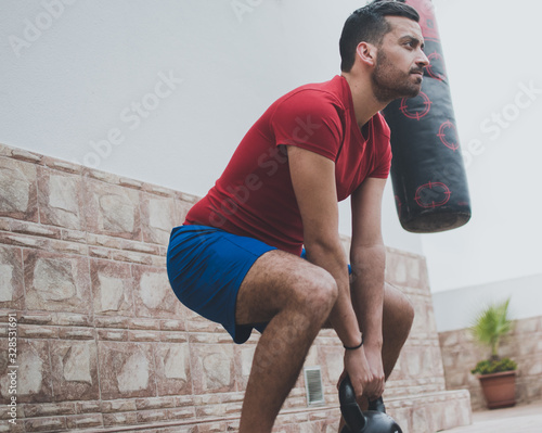 Hombre joven y guapo realizando ejercicios de fitness al aire libre Wallpaper Mural