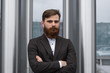 Portrait of an handsome businessman wearing jacket over office building in financial district outdoors. Young bearded Businessman outdoor. Successful entrepreneur dressed in formal wear.