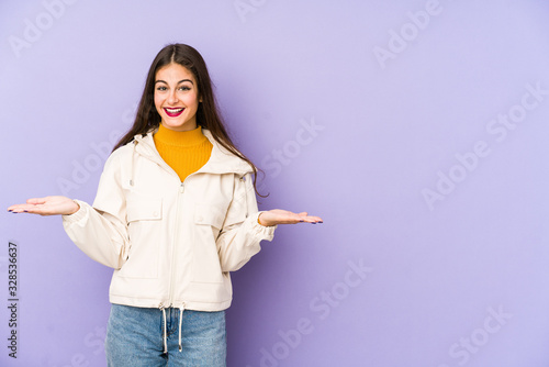 Fotografía Young caucasian woman isolated on purple background makes scale with arms, feels happy and confident