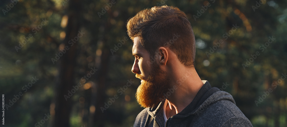 Fototapeta Close up portrait of confident bearded man in a autumn park. Profile young handsome serious bearded man Young hipster hiking forest.