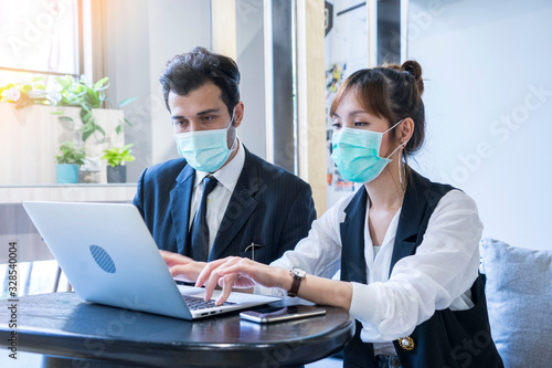 plakat sian female and Businessman workers meeting together with laptop and wear protective masks prevent PM 2.5 and corona viruus or covic19 at co working space .Health and teamwork concept