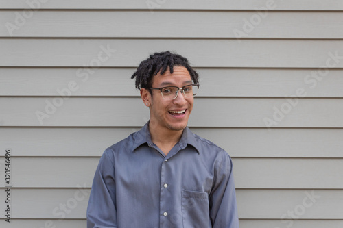 Photo Happy biracial millennial man with open smile laughing, natural dreadlocks, new