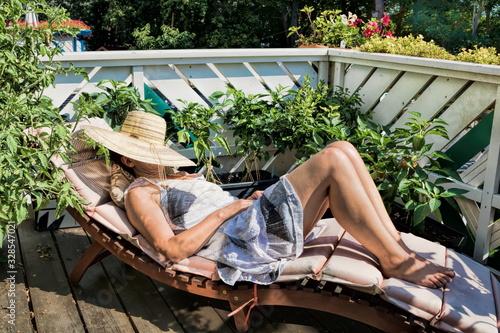 frau nimmt auf einem balkon ein sonnenbad Wallpaper Mural