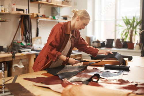 Fényképezés Young adult blond woman in casual outfit standing at table in her workshop cutti