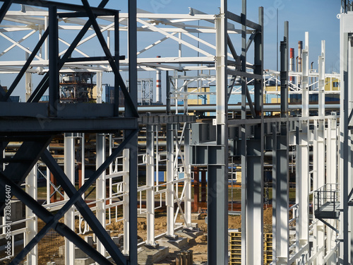 Fototapeta Work site and large steel frame of a large commercial building over petrochemical plant landscape. obraz