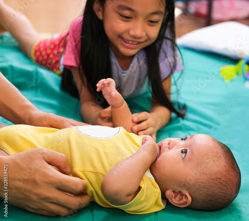 Obraz baby boy laying down on bed with caucasian girl black long hair smile with and playing fun. love in thailand family - fototapety do salonu