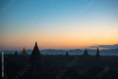 Sunrise above old pagodas misty with amazing clouds early morning and air balloons at Bagan, Myanmar Wallpaper Mural