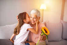 Cute Girl Giving A Bunch Of Flowers To Her Grandmother Sitting On The Couch. Happy Grandmother Hugging Small Cute Grandchild Thanking For Flowers Presented. Darling Granddaughter Always Remembers
