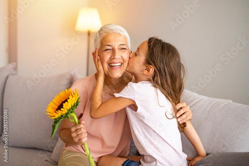 Obraz na plátne Little preschool granddaughter kissing happy older grandma on cheek giving viole