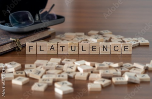 Photo flatulence concept represented by wooden letter tiles on a wooden table with gla
