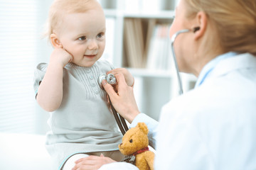 Doctor and patient in hospital. Little girl is being examined by doctor with stethoscope. Medicine concept
