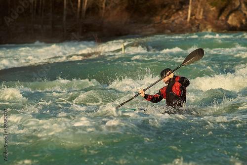 Valokuva Athlete kayaker is training in a slalom kayak boat on high water Soča river kayak track in Solkan, Slovenia