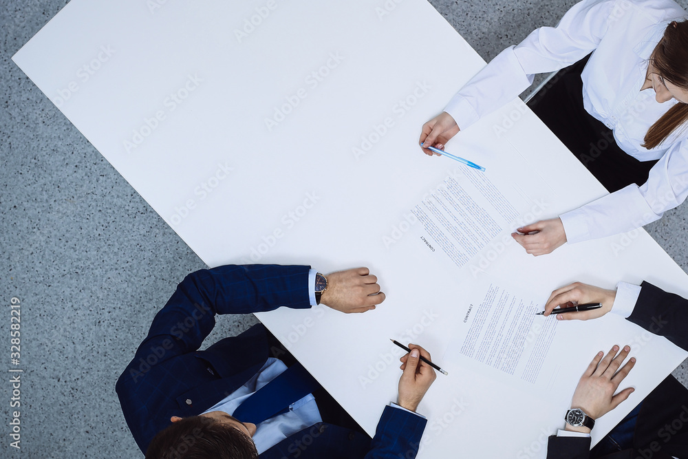 Fototapeta Group of business people and lawyer discussing contract papers sitting at the table, view from above. Businessman is signing document after agreement done