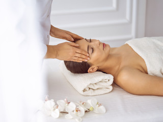 Obraz na płótnie Canvas Beautiful brunette woman enjoying facial massage with closed eyes. Relaxing treatment in medicine and spa center concepts